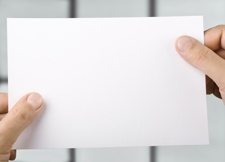 hand holding paper: White blank sheet of paper in  hands Stock Photo