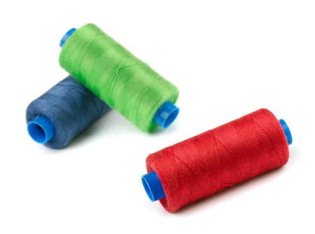 Three spools of color thread isolated on white photo