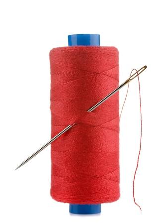 hilo rojo: Carrete de hilo y la aguja aislado en blanco Foto de archivo