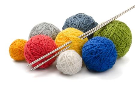 wool fiber: Bolas de colores de hilo y agujas de tejer aislado en blanco