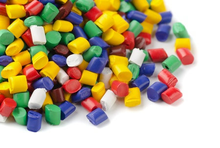 Colourful plastic polymer granules on white photo