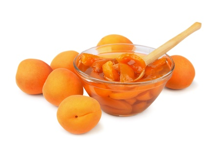 Apricot jam and some fresh apricots isolated on white photo