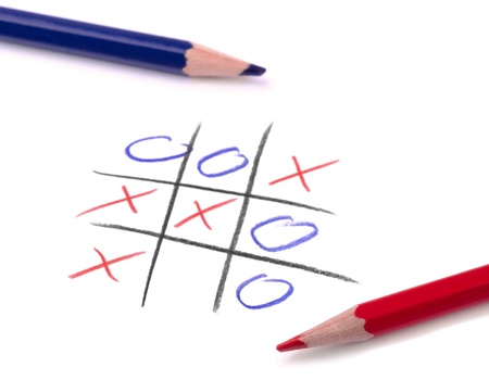 Crosses: Tic tac toe game and two pencil on white page