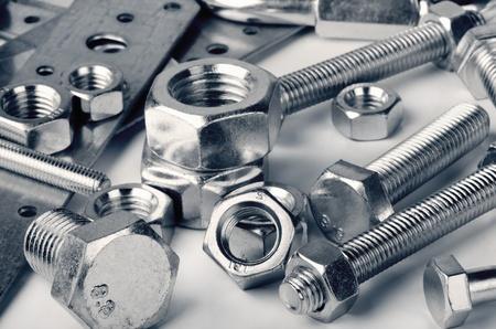 tuercas y tornillos: Primer plano de diversas tuercas de acero y pernos