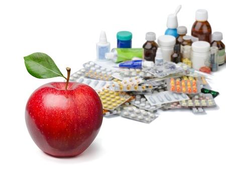 Manzana roja en frente de un gran montón de medicamentos. Concepto de estilo de vida saludable.