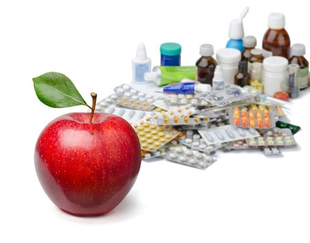 Red apple in front of a large pile of medicines. Healthy lifestyle concept.