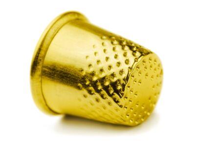 elementos de protección personal: Dedal de coser de oro aislado en blanco