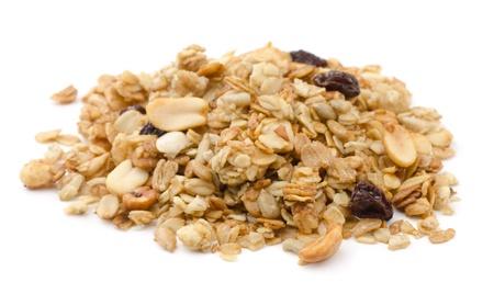 Stapel van granolagraangewas met rozijnen en noten op wit wordt geïsoleerd