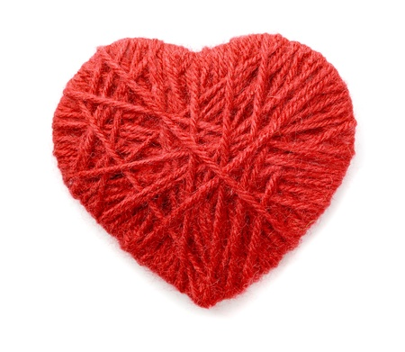 Heart made of red wool yarn isolated on white photo