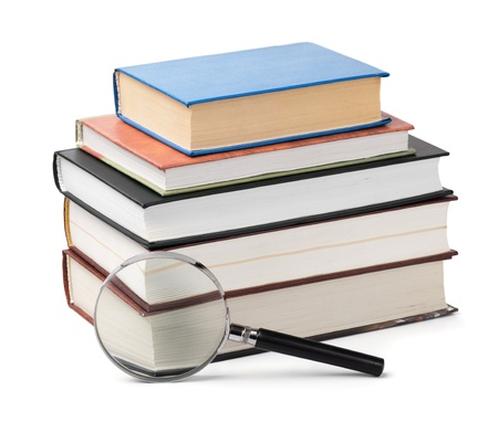 scientific literature: Magnifying glass and books stack isolated on white