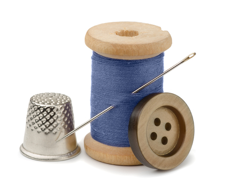 objects equipment: Spool of blue thread, needle, button  and thimble isolated on white