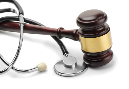 Close up of stethoscope and gavel on white background