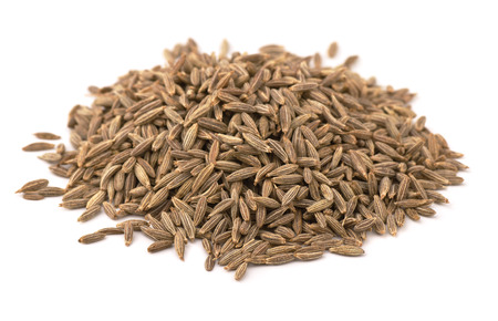 Heap of whole cumin seeds isolated on white Stock Photo