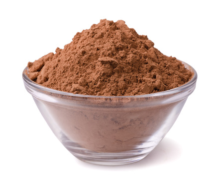 Glass bowl of cocoa powder isolated on white photo