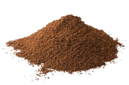 白で隔離される新鮮な挽いたコーヒー粉の杭
