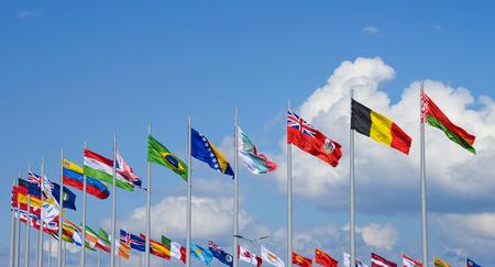 Rij van nationale vlaggen tegen de blauwe hemel