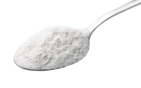 sodium hydrogen carbonate: Spoon of baking soda isolated on white