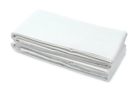 Stack bílého složeného ložního prádla izolovaných na bílém