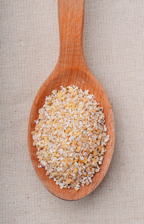 grits: Wooden spoon of barley grits