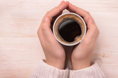 two hands: Top view of hands holding plastic coffee cup Stock Photo