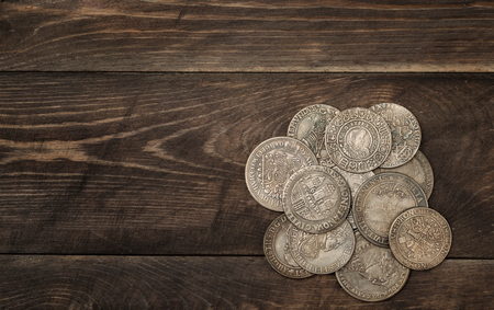 Ancient silver coins on dark wooden background