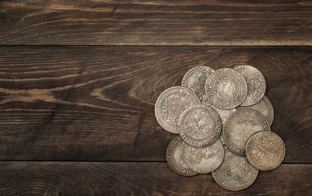 monete antiche: monete d'argento antiche su sfondo scuro in legno