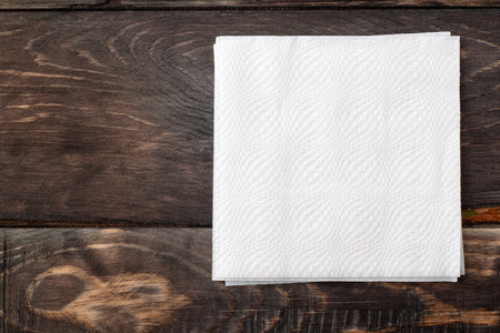 above: White paper napkins on dark wooden table surface
