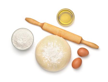 Bovenaanzicht van het deeg en het bakken ingrediënten op wit wordt geïsoleerd Stockfoto