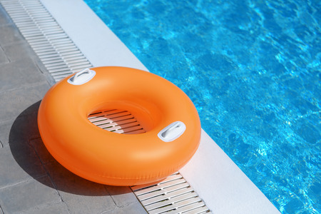 Orange swimming float ring at the poolside