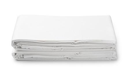 Stapel witte gevouwen beddengoed bladen geïsoleerd op wit