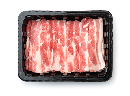 Top view of plastic disposable tray with raw sliced bacon isolated on white Stock Photo