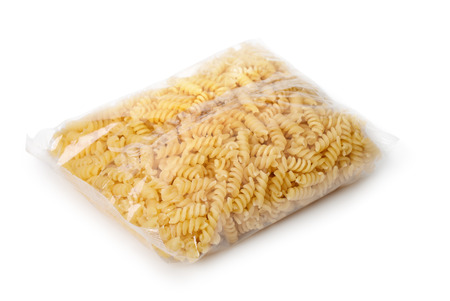 carbohydrates: Transparent plastic bag of fusilli pasta isolated on white Stock Photo