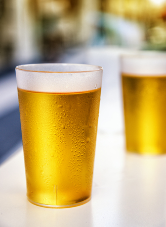 Two misted plastic beer cups outdoor