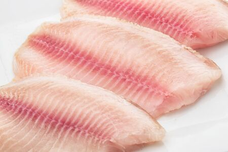Close up of raw fresh tilapia fillet  on white plate Stock Photo