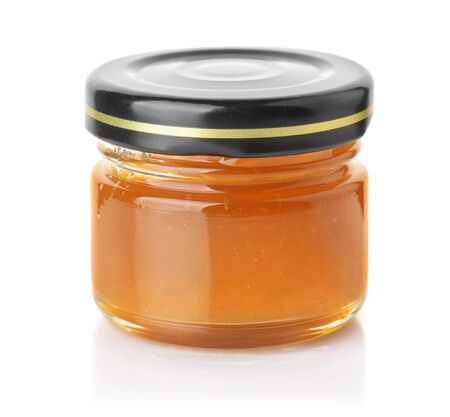 Small glass jar of apricot jam isolated on white Stock Photo