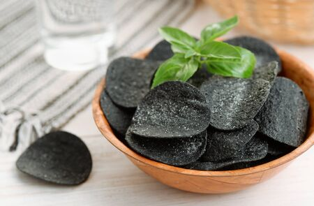 Black spicy potato chips in wooden  bowl