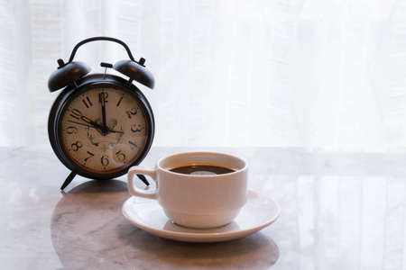 coffee hour: coffee cup on mable table with alarm clock concept working hour