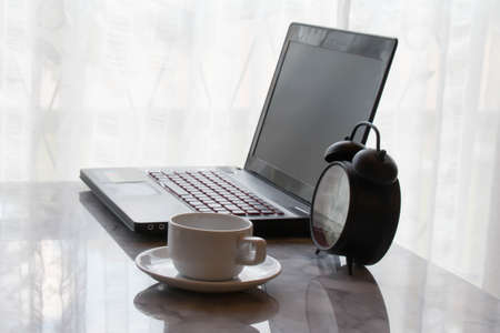 working hour: Coffee cup and laptop with alarm clock for business office table concept working hour