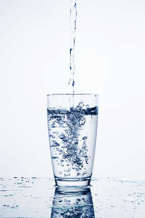 Water falling in glass on isolate background.