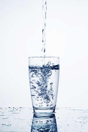 Woda spadająca w szkle na tle izolowania.