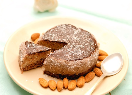 Homemade raw-vegan sliced cake on a brown plate with almonds and coconut flakes photo