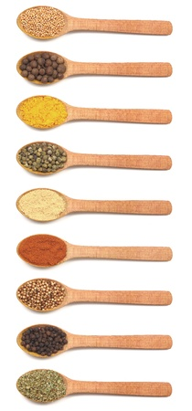 Group of wooden spoons filled with various spices isolated on white background photo