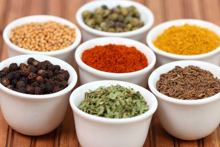 Collection of spices on white pots over a bamboo table Stock Photo - 16442290