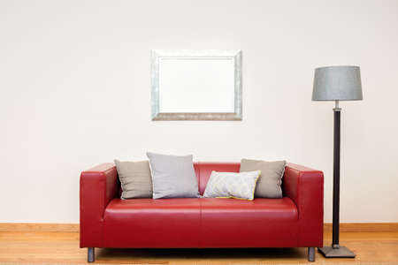 Tuxedo leather sofa in red with mirror and lamp. Stock Photo