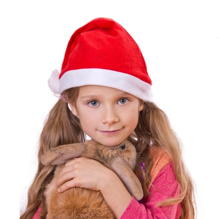 weihnachten: girl on christmas with a red cap and a rabbit