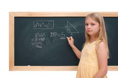 Schulmädchen direkt vor dem Tafel mit einer mathematischen Aufgabe Standard-Bild - 12029568