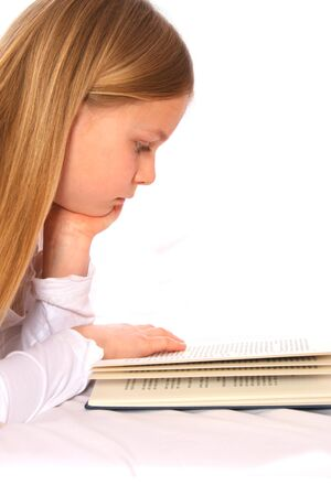 nger: Young girl  with long, fair hair is reading a book. Stock Photo