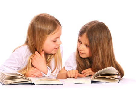 Two young girls  with long, fair hair are reading books.
