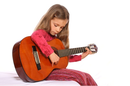 beginner: A young girl is playing a guitar.