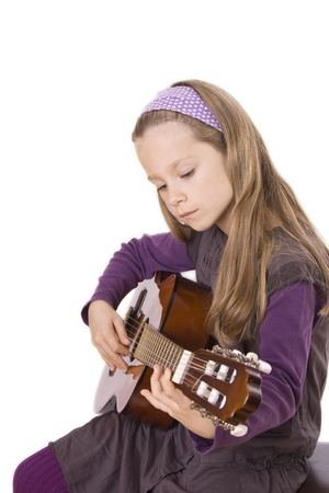 musik: A young girl with long hair is playing guitar. Stock Photo